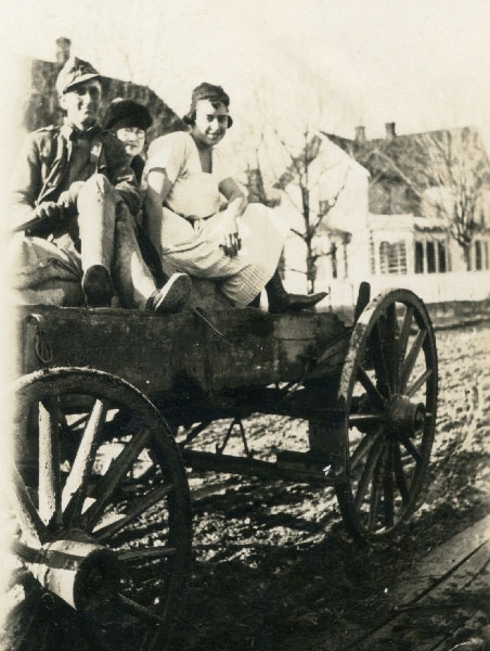 Unidentified man and two women in a wooden wagon on dirt street in front of the McComb Store in Huntersville, W.Va. - ca. 1915